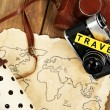 Retro camera on world map with word Travel on wooden table background — Stock Photo #67203863