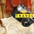 Retro camera on world map with word Travel on wooden table background — Stock Photo #67203869