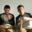 Two handsome young men playing video games in room — Stock Photo #67204663