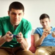 Two handsome young men playing video games in room — Stock Photo #67204669