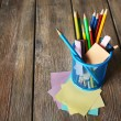 Colorful pencils in metal holder with sticky notes on wooden planks background — Stock Photo #67205025