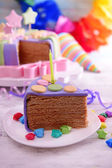 Delicious piece of birthday cake on table on bright background — Stock Photo
