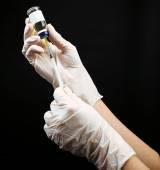 Hands in gloves filling medicine from ampule into syringe on black background — Stock Photo