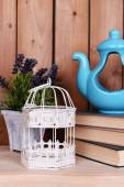 Interior design with decorative pot, cage, plant and stack of books on tabletop on wooden planks background — Stockfoto