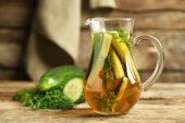 Glass ewer with fresh organic cucumber water on wooden table — Fotografia Stock