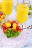 Fruit salad with mint and orange juice in glassware on color wooden background — Stock Photo