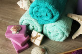 Spa composition with towels and soap on wooden background — Stock Photo