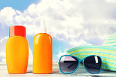 Bottles of suntan cream with sunglasses and hat on table isolated on white — Stockfoto