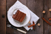 Tasty piece of chocolate with lump sugar and cinnamon sticks cake on wooden table background — Stock Photo