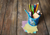 Colorful pencils in metal holder with sticky notes on wooden planks background — Stock Photo