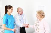 Happy doctors and patients in hospital clinic — Stock Photo
