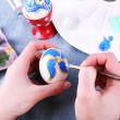 Painting Easter eggs by female hands on colorful tablecloth background — Stock Photo #67277807
