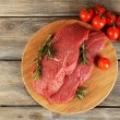 Raw beef steak with rosemary and cherry tomatoes on cutting board on wooden background — Stock Photo #67275613