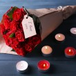 Bouquet of red roses with tag wrapped in paper and candles on wooden background — Stock Photo #67276059