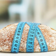 Fresh bread with measuring tape, on wooden table- diet concept — Stock Photo #67278927