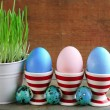 Fresh green grass in small metal bucket and Easter eggs in holders, on wooden background — Stock Photo #67279707