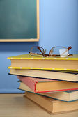 Stack of books with glasses on wooden desk, on colorful wall and blackboard background — Stock Photo