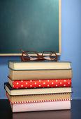 Stapel von Büchern mit Brille auf Holz-Schreibtisch, auf bunte Wand und Tafel-Hintergrund — Stockfoto