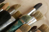 Different paintbrushes on fabric background — Stock Photo