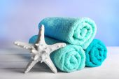 Rolled towels with starfish on wooden table and light colorful background — Stock Photo