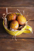 Easter eggs in mug on wooden background — Stock Photo