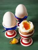 Boiled eggs in holders on color wooden background — Stock Photo