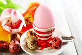Easter egg in houder en tulp bloemen op houten achtergrond — Stockfoto