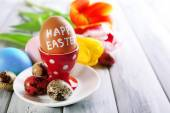 Easter eggs in holders and tulip flowers on wooden background — Stock Photo