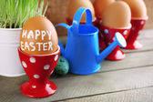 Fresh green grass in small metal bucket and Easter eggs in holders, on wooden background — Stock fotografie