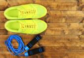Shoes and sports equipment on wooden floor, top view — Stock Photo