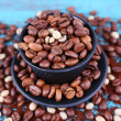 Coffee beans in black ceramic cup on blue wooden background — Stock Photo #67449913