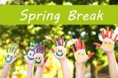 Spring break concept. Smiling colorful hands on nature background — Stock Photo