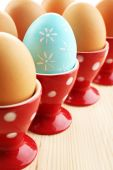 Boiled eggs in holders on wooden table background. Easter concept — Stock Photo
