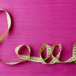 Love word formed with measuring tape on purple background — Stock Photo #67450007