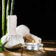 Beautiful composition with massage bags and candle on table on dark background — Stock Photo #67450445