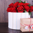 Bouquet of red roses in textile box with present on wooden background — Stock Photo #67450701