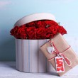 Bouquet of red roses in textile box with present on wooden background — Stock Photo #67450709
