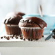 Tasty homemade chocolate muffins and cup of coffee on wooden table, on light background — Stock Photo #67452361