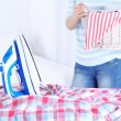 Electric iron and shirt on ironing board in room — Stock Photo #67455175