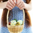 Beautiful little girl holding wicker basket with Easter eggs, close-up, isolated on white — Stock Photo #67455321
