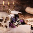 Still life with human skull, retro book and candlelight on wooden table, closeup — Stock Photo #67455393