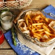 Tasty french fries and fresh potatoes in metal baskets on wooden table background — Stock Photo #67456069