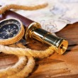 Marine still life spyglass, compass, rope and world map on wooden background — Stock Photo #67458193