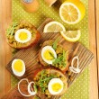 Sandwiches with green peas paste and boiled egg on cutting board with napkin on wooden planks background — Stock Photo #67458261