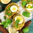 Sandwiches with green peas paste and boiled egg on cutting board with napkin on color wooden background — Stock Photo #67458263
