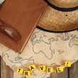 Straw hat, book and glasses with word Travel on world map and wooden planks background — Stock Photo #67459711