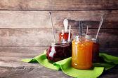 Jars of tasty jam with napkin on wooden background — Stock Photo