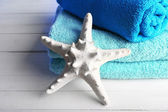 Terry towels with starfish on wooden table background — Stock Photo