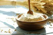 Bowl of flour with spoon and napkin on wooden table, closeup — Stock Photo