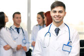 Attractive male doctor with team in conference room — Stock Photo